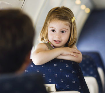 young girl leaning over seat talking to adults